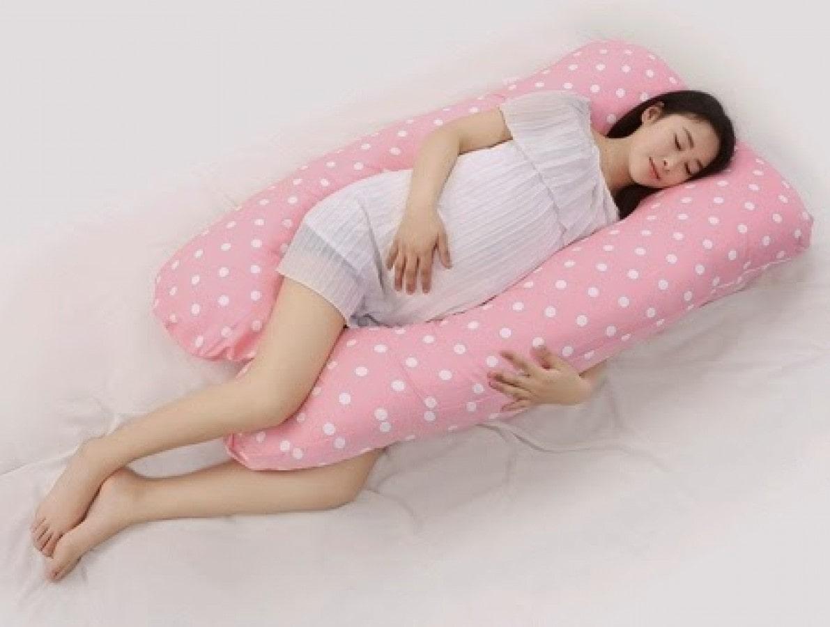 Ngủ đúng tư thế cùng với sự hỗ trợ của gối bầu là cách trị đau lưng cho bà bầu hiệu quả.